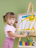 Baby paints at the easel Royalty Free Stock Photos