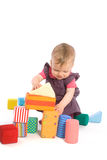 Baby palying with toy blocks. TOYS ARE PROPERTY RELEASED. Little baby girl (9 months old) playing with toy blocks. Isolated on white royalty free stock images