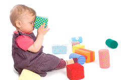 Baby palying with toy blocks. TOYS ARE PROPERTY RELEASED. Little baby girl (9 months old) playing with toy blocks. Isolated on white royalty free stock photos