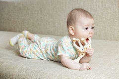 Baby palying with toy giraffe Stock Photo