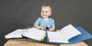 Baby with paperwork at wooden desk Royalty Free Stock Photography