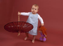 Baby with parasol. Baby, 1 year old with puppet and parasol. Studio shot Royalty Free Stock Images