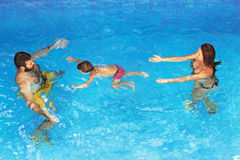 Baby with parents diving underwater in outdoor pool Royalty Free Stock Photos
