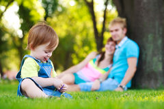 Baby playing with parents in a beautiful park Royalty Free Stock Photo