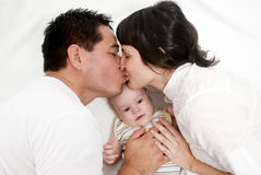 Baby with parents lying on a bed Stock Photo