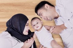 Baby and parents lying on wooden floor Royalty Free Stock Images