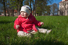 Baby in park. Little baby girl sitting on fresh spring grass in park Stock Photos