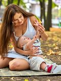 Baby in park outdoor. Kid on mom`s hands. Happy beautiful mom and child with leaf sitting on ground in autumn foliage Royalty Free Stock Images