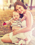 Baby in park outdoor. Kid on mom`s hands. Happy beautiful mom and child sitting on ground in sunrise or sunset . Color tone on shiny sunlight background Stock Image