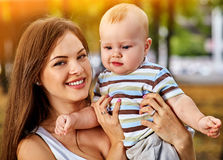 Baby in park outdoor. Kid on mom`s hands. Happy beautiful mom and child summer sunrise or sunset on city outside. Portrait of happy loving mother and her son Royalty Free Stock Image