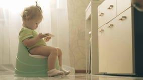 Baby passt Karikatur auf dem Smartphone beim Sitzen auf dem Töpfchen auf stock footage