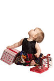 Baby in patchwork dress holds gifts and looks up. Curious baby in velvet embroidered patchwork dress sits with festive holiday gifts, tilts head back and looks stock photography