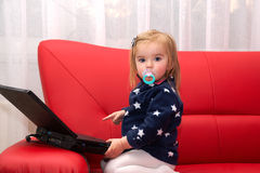 Baby pc. Baby with computer in home on a red couch Stock Photography