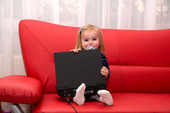 Baby pc. Baby with computer in home on a red couch Royalty Free Stock Photography