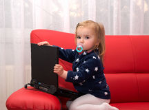 Baby pc. Baby with computer in home on a red couch Stock Image