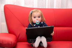 Baby pc. Baby with computer in home on a red couch Stock Images