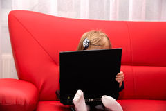 Baby pc. Baby with computer in home on a red couch Royalty Free Stock Image