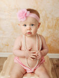 Baby with pearl necklace. Adorable young baby girl wearing a vintage pearl necklace and pink rose headband Stock Photo