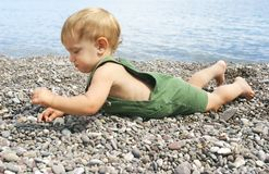 Baby on pebble beach. Baby playing with stones on pebble beach Stock Photo