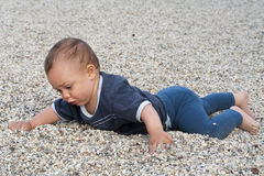 Baby in pebbles Stock Image