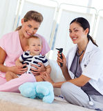 Baby with pediatrician and nurse. In hospital smiling at the camera Stock Photos
