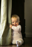 Baby peek-a-boo. Baby in pajamas playing peek-a-boo with curtain stock photos