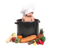 Baby Peeking Through a Chef Hat. Cute Baby Peeking Through a Chef Hat While Taking a Portrait in a Cooking Pot Themed Set Royalty Free Stock Image