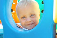 Baby Peeking at Playground Stock Image