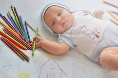 A baby with pencils. The child draws. royalty free stock image