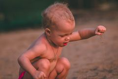 Baby With Pendant Necklace Holding Sand at Daytime Stock Images