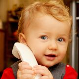 Baby at the phone. Portrait of cute blond baby boy talking at the phone Stock Photos