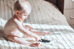 Baby with the phone sitting on bed Royalty Free Stock Photo