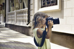 Baby with a photo camera takes pictures. Royalty Free Stock Image