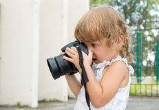 Baby with a photo camera takes pictures. Stock Photos