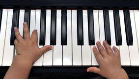 Baby pianist. A babies hands playing the piano Stock Image