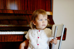 Baby and piano Stock Images