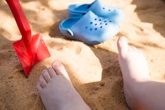 baby& x27; piernas de s en la arena de la playa, chancletas azules y una pala del juguete, juego en la salvadera fotos de archivo libres de regalías