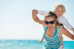 Baby piggybacking mother on beach Royalty Free Stock Photography