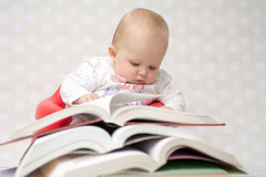 Baby with pile of books. Cute baby girl reading behind a pile of books Stock Image