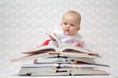 Baby with pile of books. Cute baby girl sitting behind a pile of books Royalty Free Stock Photography