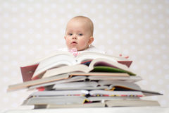 Baby with pile of books. Cute baby girl sitting behind a pile of books Stock Photo