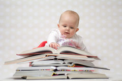 Baby with pile of books Stock Image