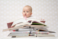 Baby with pile of books. Cute baby girl sitting behind a pile of books Royalty Free Stock Photos