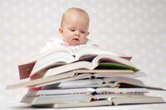 Baby with pile of books. Cute baby girl sitting behind a pile of books Royalty Free Stock Images