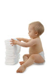 Baby with pile of diaper. Baby sitting with pile of diaper on white background Royalty Free Stock Photos