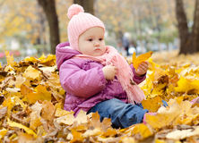 Baby in a pile of leaves. Little cute girl sitting in a pile of yellow leaves stock images