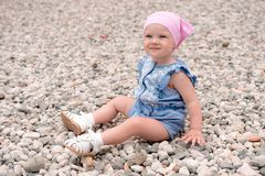 Little girl sitting on the beach with sea pebbles in blue suit a. The baby in a pink cap, blue overalls, white socks and sandals sits on a large number of small stock photos