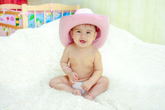 Baby in a pink cowboy hat sitting in diapers on the couch stock photos