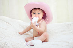 Baby in a pink cowboy hat sitting in diapers on the couch royalty free stock photos