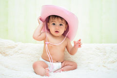 Baby in a pink cowboy hat sitting in diapers on the couch royalty free stock photography